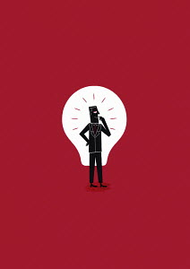 Confident businessman in front of lightbulb
