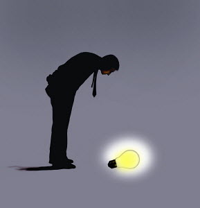 Man looking down on glowing light bulb