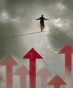 Man walking tightrope over arrows in cloudy sky