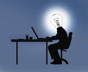 Businessman working at desk with light bulb head