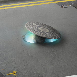 Man peeping out from manhole in road