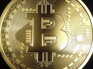 Extreme close up of single shiny new gold bitcoin