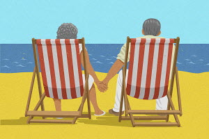 Senior couple sitting hand in hand in deckchairs on beach