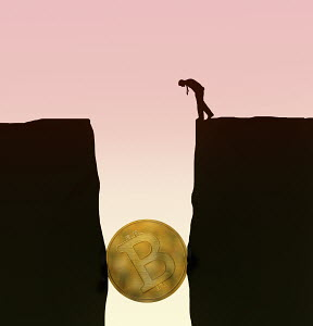 Businessman looking down at bitcoin stuck between cliffs