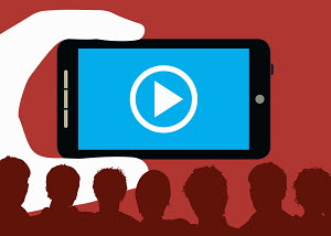 Large hand holding smart phone with play button in front of audience