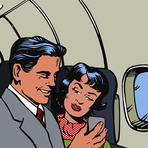 Man and woman reading message on smart phone on plane