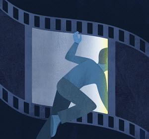 Man climbing through camera film