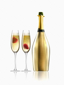 Two glasses of champagne with strawberries next to gold champagne bottle