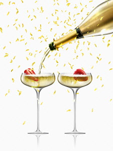Confetti falling on gold champagne bottle filling two champagne coupes