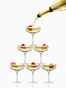 Gold champagne bottle filling coupe glasses in champagne pyramid