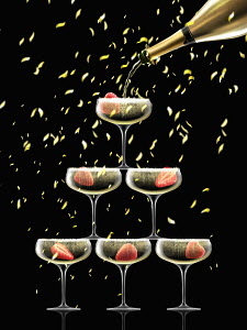 Confetti falling on coupe glasses in champagne pyramid