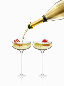 Gold champagne bottle filling coupe glasses containing strawberries
