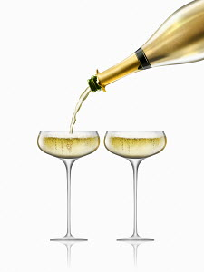Gold champagne bottle filling two champagne glasses