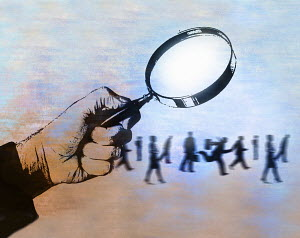 Man examining business people under magnifying glass