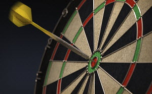 Dart hitting bull's eye on dartboard