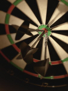 Three darts hitting bull's eye on dartboard