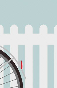 Close up of bike wheel against white fence