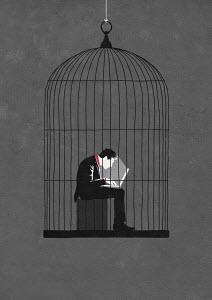 Businessman working at night in birdcage