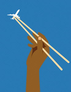 Hand catching aeroplane in chopsticks
