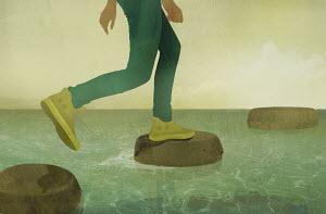 Legs of teenage boy walking across stepping stones