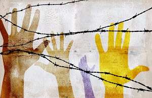 Hands reaching up behind barbed wire