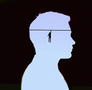 Man dangling from tightrope inside of man's head