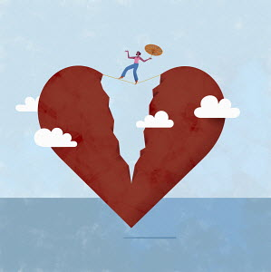 Woman balancing on tightrope over broken heart