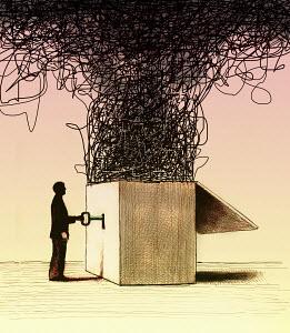 Businessman unlocking large tangle from box