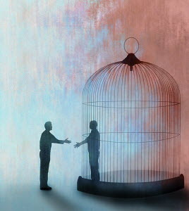 Man shaking hands with man trapped inside of cage