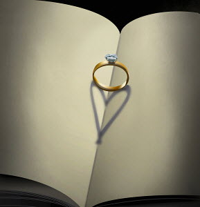 Engagement ring with heart shaped shadow on open book