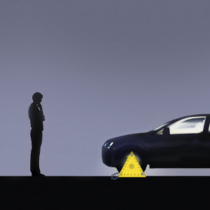 Man looking at clamped car