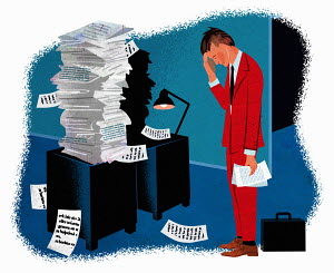 Businessman in despair at pile of paperwork