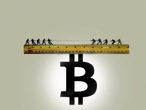 Tug of war on top of ruler balanced on bitcoin sign
