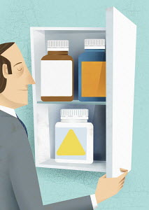 Tired man choosing pill bottle from medicine cabinet