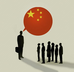 People listening to larger businessman talking with Chinese flag speech bubble