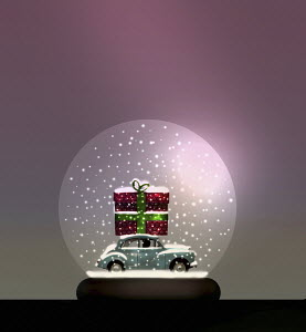 Car with huge Christmas present on roof inside of snow globe