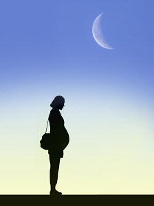 Moon in sky above silhouette of pregnant woman