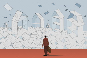 Conveyancing lawyer looking at piles of paper forming houses