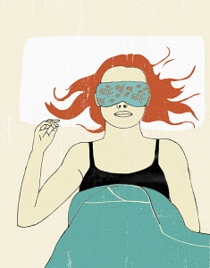 Woman in bed wearing sleep mask