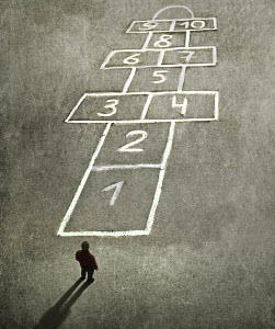Overhead view of man standing in front of hopscotch game