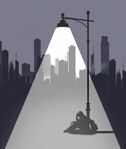 Street light shining on man sitting on ground in despair