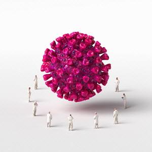 Healthcare workers surrounding giant computer generated coronavirus