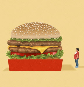 Overweight boy looking at giant cheeseburger