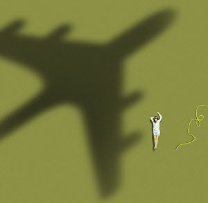 Woman relaxing on lawn waving at passing aeroplane