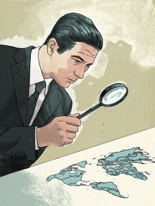 Businessman examining map of the world through magnifying glass