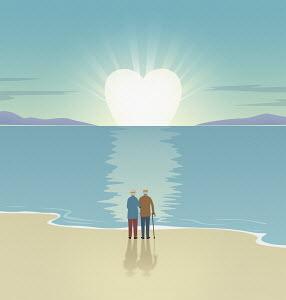 Elderly couple watching heart shaped sun setting