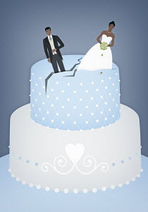 Bride and groom on top of cracking wedding cake