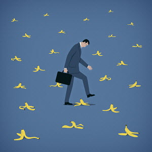 Businessman avoiding lots of banana skins
