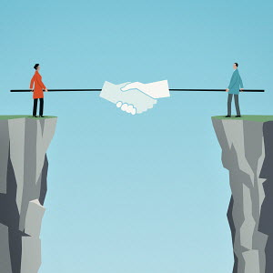 Businessman and businesswoman shaking hands with poles over gap between cliffs