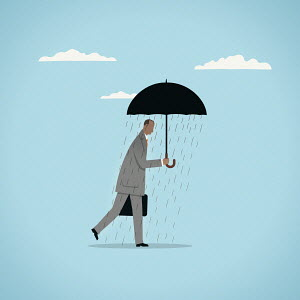 Rain falling from under umbrella on businessman